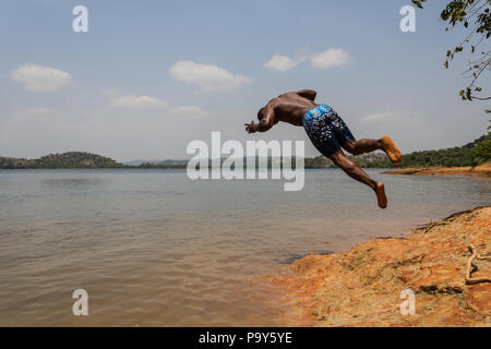A young muscular athletic man takes a somersault dive into the river in the morning. - Stock Photo