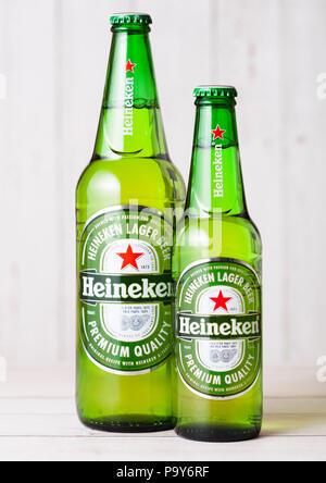 LONDON, UK - APRIL 27, 2018: Bottles of Heineken Lager Beer on wooden background. Heineken is the flagship product of Heineken International - Stock Photo