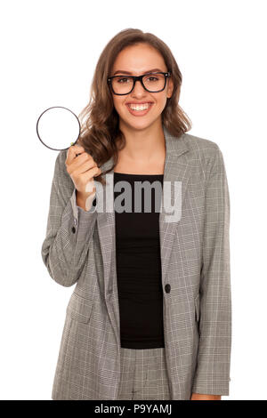 Beautiful young happy woman looking trough the magnifying glass - Stock Photo
