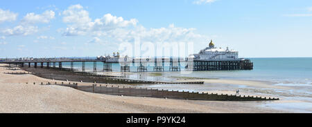 Panoramic view of the Victorian Eastbourne pier in East Sussex, UK on a sunny summers day with the beach at low tide in the foreground - Stock Photo