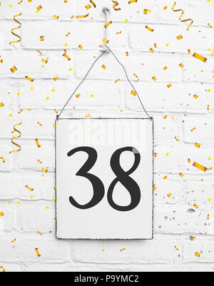 Thirty eight 38 years old birthday congratulations text with golden confetti sign white brick background - Stock Photo
