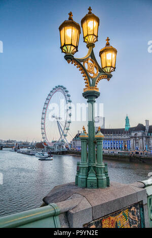 A lamp standard on Westminster bridge, illuminated, with the London Eye and County Hall in the background. - Stock Photo