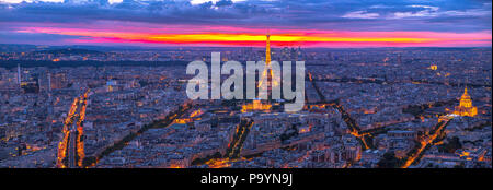 Paris, France - June 30, 2017: Tour Eiffel and national residence of the Invalids at twilight red sky panorama from Observatory Deck Tour Montparnasse. Aerial view of Paris skyline. Night urban scene. - Stock Photo