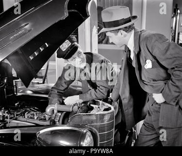 1930s 1940s AUTO MECHANIC EXPLAINING PROBLEM WITH ENGINE TO CAR OWNER  - m2940 HAR001 HARS COPY SPACE HALF-LENGTH PERSONS AUTOMOBILE CARING MALES FIXING TRANSPORTATION MIDDLE-AGED B&W MIDDLE-AGED MAN SKILL SUIT AND TIE OCCUPATION SKILLS EXPLAINING OWNER CUSTOMER SERVICE SERVICE STATION OCCUPATIONS REPAIRING AUTOMOBILES SUPPORT VEHICLES MID-ADULT MID-ADULT MAN SOLUTIONS BLACK AND WHITE CAUCASIAN ETHNICITY HAR001 OLD FASHIONED - Stock Photo