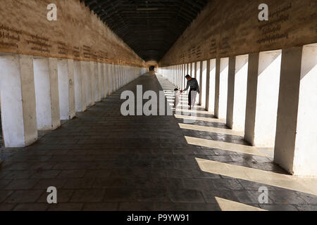 Father and son in covered walkway to Shwezigon pagoda, Nyaung-U - Stock Photo