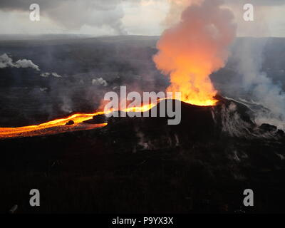 Lava and ash pour out from fissure 8 as a lava channel flows toward the ocean caused by the Kilauea volcano eruption July 14, 2018 in Hawaii. - Stock Photo