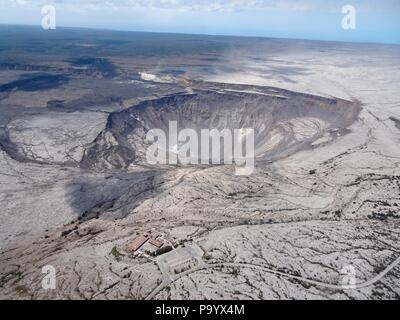 Aerial photo of Halemaumau and part of the Kilauea caldera floor at the summit as the volcano continues to erupt July 13, 2018 in Hawaii. In the lower third of the image, you can see the buildings that housed the USGS Hawaiian Volcano Observatory and Hawaii Volcanoes National Park Jaggar Museum. - Stock Photo