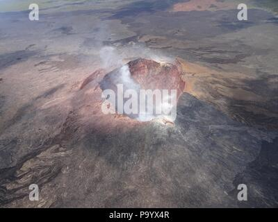 Aerial photo of Halemaumau and part of the Kilauea caldera floor at the summit as the volcano continues to erupt July 17, 2018 in Hawaii. In the lower third of the image, you can see the buildings that housed the USGS Hawaiian Volcano Observatory and Hawaii Volcanoes National Park Jaggar Museum. - Stock Photo