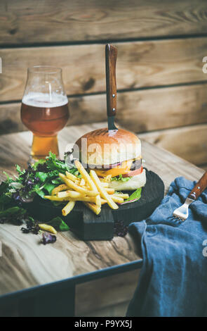 Classic burger dinner with glass of beer and french fries - Stock Photo