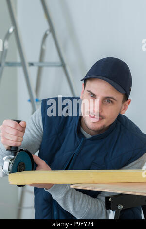 handsome carpenter using grinder on plank - Stock Photo