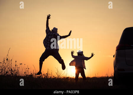 Father and son playing in the park at the sunset time. People having fun outdoors. Concept of summer vacation and friendly family. - Stock Photo