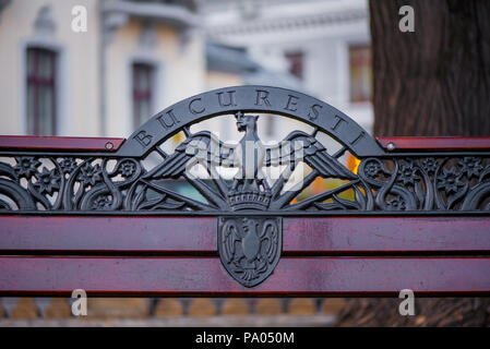 Wooden bench decorated with abstract ornaments in central park of Bucharest. ('Bucuresti' means Bucharest in english) - Stock Photo