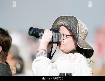 Lady wearing large hat photographing the RAF RIAT air show Fairford 2018 - Stock Photo
