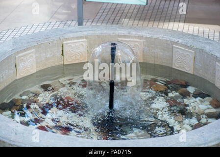 Small indoor fountain in a pool with decorative stones, pebbles and rocks. Clean water - Stock Photo
