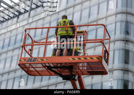 man in a cherry picker or mobile elevated work platform MEWP. city hall london. - Stock Photo