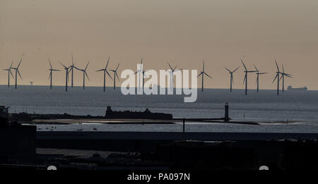 The sun sets over The Burbo Bank Offshore Wind Farm on the River Mersey behind Fort Perch Roick and New Brighton Lighthouse. - Stock Photo