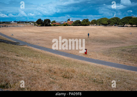 Dry brown grass field on Southsea Common public park due to the extreme hot weather this year. - Stock Photo