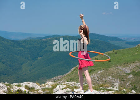 Young woman in pink skirts rotates hula hoop at the mountain top on beautiful nature background. Healthy lifestyle and love for fitness and sport. Fre - Stock Photo