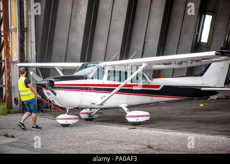 Single engine aircraft, ultra light plane ready for flight. Pilot is pulling out small motor air plane out from hangar in an old airport. Private airp - Stock Photo