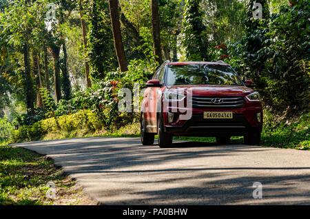 Front view of red Hyundai Creta SUV on a beautiful road through plantation leading to Chiklihole Reservoir in Kushalnagar, Kodagu, Karnataka, India - Stock Photo
