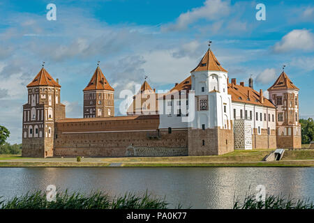Mir castle complex in the city of Mir in Belarus against a blue sky and a pond in the foreground. - Stock Photo