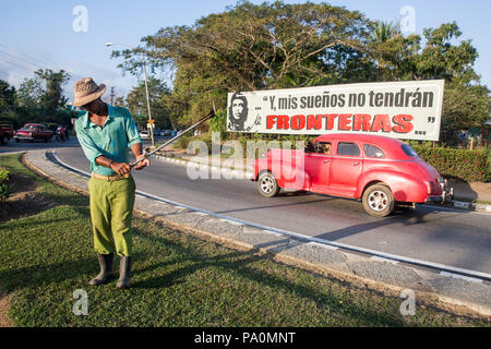 Full length shot of man cutting lawn on roadside, Pinar del Rio, Cuba - Stock Photo