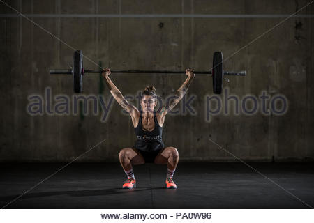 Front view shot of strong woman doing overhead squat with barbell while exercising in gym - Stock Photo