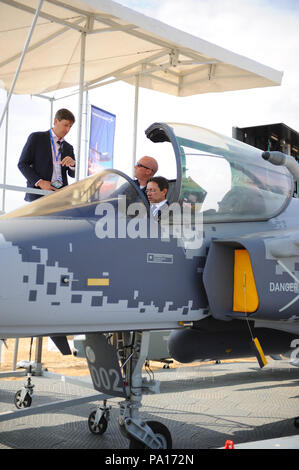 Farnborough, Hampshire, UK. 19th July, 2018. Buyers sitting in the cockpit of a full scale mock up of a Saab JAS 39 Gripen light single-engine multirole fighter aircraft on day four of the Farnborough International Airshow (FIA) which is taking place in Farnborough, Hampshire, UK.  The air show, a biannual showcase for the aviation industry, is the biggest of it's kind and attracts civil and military buyers from all over the world. trade visitors are normally in excess of 100,000 people. Credit: Michael Preston/Alamy Live News - Stock Photo