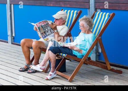Bournemouth, Dorset, UK. 20th July 2018. UK weather: hot and humid with hazy sunshine at Bournemouth, as sunseekers head to the seaside at Bournemouth beaches to enjoy the fine weather. Senior couple sitting in deckchairs on Bournemouth pier, the man reading The Sun newspaper.  Credit: Carolyn Jenkins/Alamy Live - Stock Photo