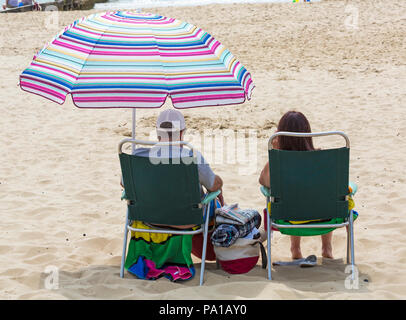 Bournemouth, Dorset, UK. 20th July 2018. UK weather: hot and humid with hazy sunshine at Bournemouth, as sunseekers head to the seaside at Bournemouth beaches to enjoy the fine weather. Couple sitting in chairs under colourful parasol.  Credit: Carolyn Jenkins/Alamy Live News - Stock Photo