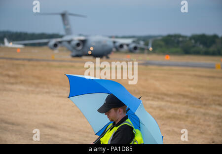Farnborough, Hampshire, UK. 20 July, 2018. Final day of the biennial Farnborough International Trade Airshow FIA2018, typically a transition day as business customers leave in VIP jets and members of the public arrive to watch the build-up for the weekend public airshow. A security guard is oblivious to the large Boeing C-17 Globemaster III military transport aircraft of the US Air Force parking up behind him. Credit: Malcolm Park/Alamy Live News. - Stock Photo