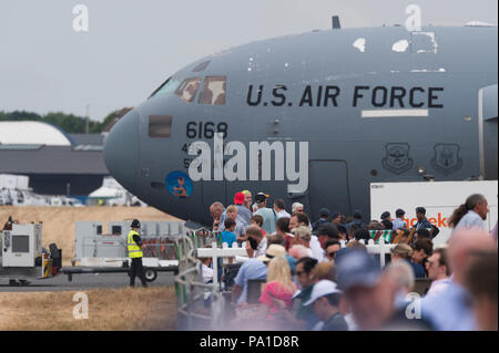 Farnborough, Hampshire, UK. 20 July, 2018. Final day of the biennial Farnborough International Trade Airshow FIA2018, typically a transition day as business customers leave in VIP jets and members of the public arrive to watch the build-up for the weekend public airshow. A large Boeing C-17 Globemaster III military transport aircraft of the US Air Force parks up, towering over spectators Credit: Malcolm Park/Alamy Live News. - Stock Photo