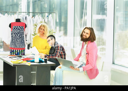 fashion designer working on a laptop in a creative office - Stock Photo