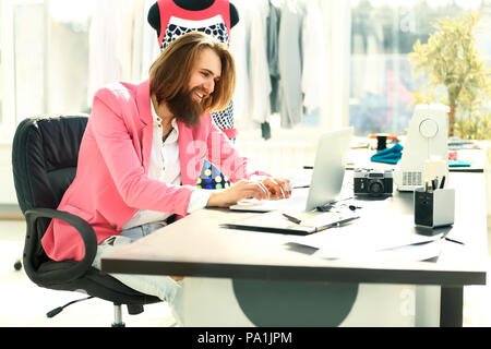 Concentrated man working on laptop and doing home design - Stock Photo