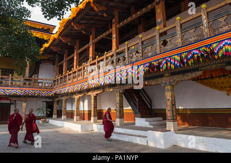 Punakha, Bhutan - April 10, 2016: Monks around the large white-washed stupa and bodhi tree in the first courtyard of Punakha Dzong, Bhutan - The Punak - Stock Photo