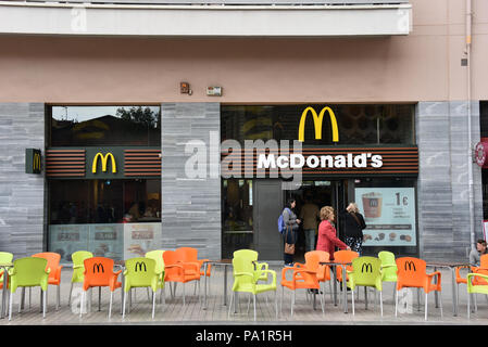 Barcelona, Spain - May 13, 2018:  McDonalds restaurant with chairs and tables on the sidewalk of street across from the Sagrada Familia. - Stock Photo