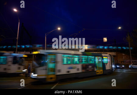 A man stands still waiting for a tram as two trams pass in either direction in front and behind him. A train passes on the bridge just overhead. - Stock Photo