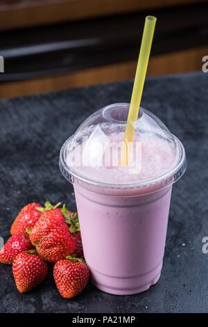 Strawberry milk shake to take away with straw on a dark background - Stock Photo