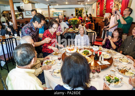 Orlando Florida Chinatown Lam's Garden Chinese restaurant dim sum ethnic dining large family lazy Susan table Asian man woman special event celebratio - Stock Photo