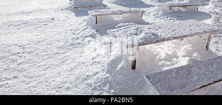 Winter snow loadings banner. Sun shining on desks and benches completely covered under deep snowfall. - Stock Photo