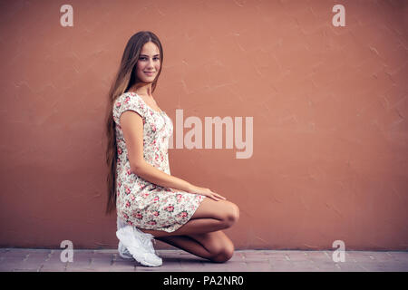 Pretty girl on the street, nice female with long natural hair sitting on blank monophonic wall background, authentic genuine beauty of young people - Stock Photo