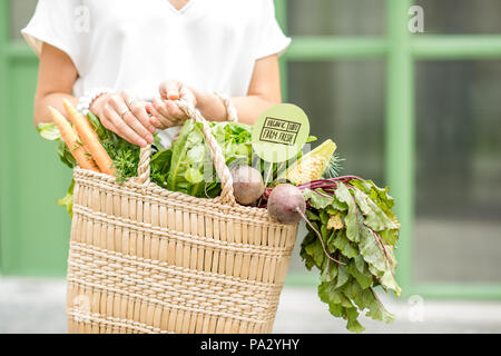Holding bag full of fresh organic vegetables from the local market on the green background - Stock Photo