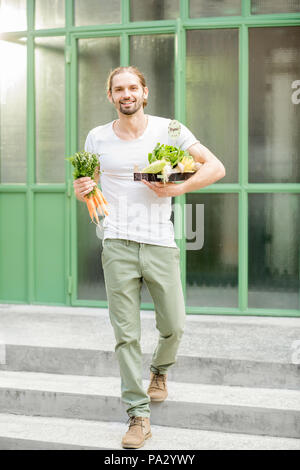 Man carrying box full of fresh raw vegetables just bought at the local market outdoors on the green background - Stock Photo
