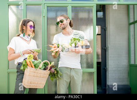 Young vegetarian couple standing together with bag and box full of fresh raw products from the local market outdoors on the green background - Stock Photo