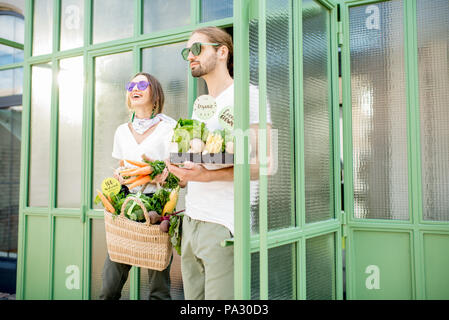 Young vegetarian couple going out the market holding bag and box full of just bought fresh products - Stock Photo