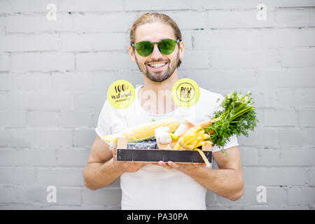 Portrait of a handsome man holding box full of fresh vegetables on the brick wall background - Stock Photo