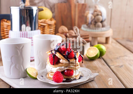 Sweet home punkcakes with white cream and fresh red raspberry berries. Two glasses of tea for breakfast and a kettle. on a wooden background. free space for text or advertising. - Stock Photo