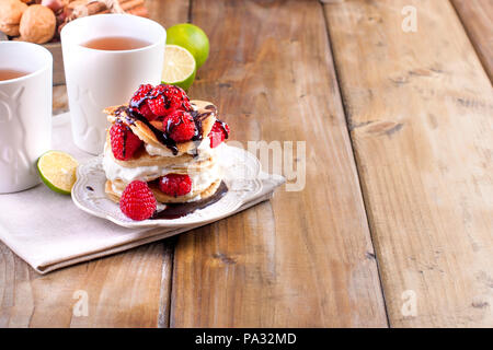 Sweet home punkcakes with white cream and fresh red raspberry berries. Two glasses of tea for breakfast. on a wooden background. free space for text or advertising - Stock Photo