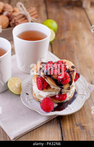Sweet home punkcakes with white cream and fresh red raspberry berries. Two glasses of tea for breakfast. on a wooden background. free space for text or advertising. - Stock Photo