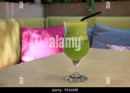 A glass of frozen lemonade mixed with fresh mint over a colorful background. - Stock Photo